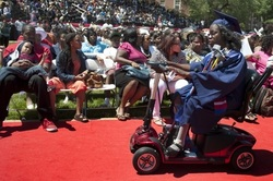 Photo from Washington Post of Britney Wilson using electric wheelchair at graduation, rolling up a red carpet